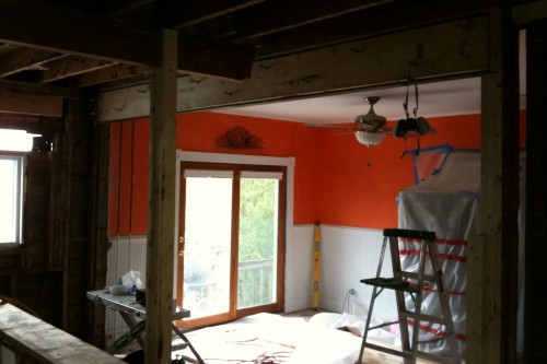A photo of a Barre kitchen during the remodeling project stripped to studs with a view towards a large sliding glass door