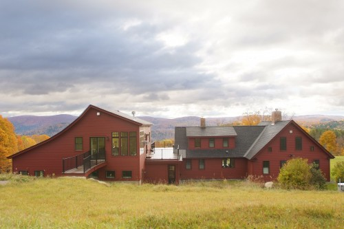 Far view of red house after completion of total home remodeling project in central vermontunder cloudy sky