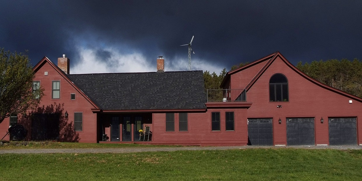 Exterior view of sprawling red central vermont house after completion of remodeling project under dark clouds