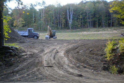 Muddy field in central vermont with work vehicles during new home build project by allied contractors