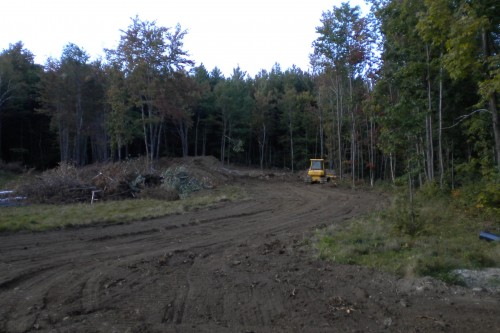 Muddy field in central vermont with bulldozer during initial stages of new home build project by allied contractors