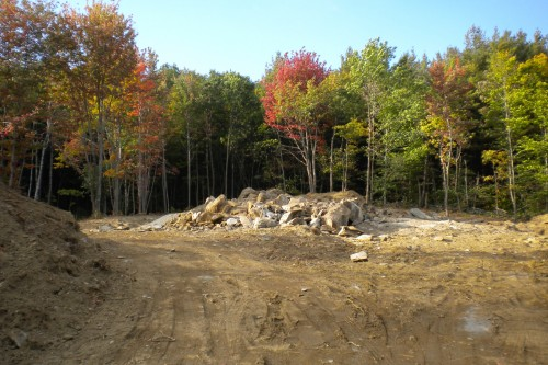 central vermont field with pile of debris and early autumn trees during new home build project by allied contractors