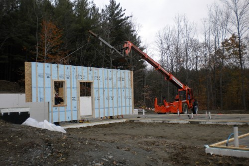 An allied contractor red crane installs a wall section during a new home installation in central vermont