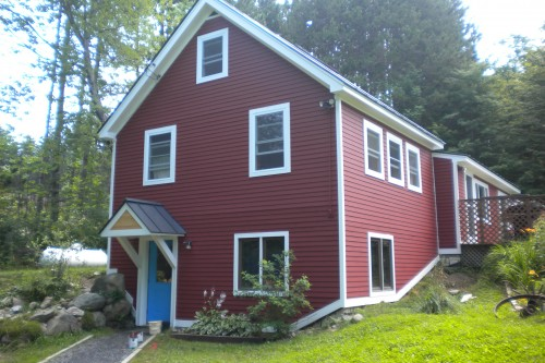 Red house with white trim after central vermont home remodeling project by allied building contractors