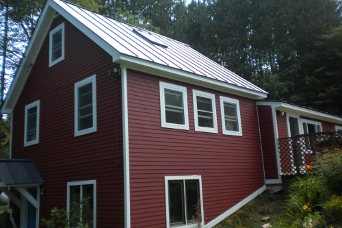 Side of red house with white trim after siding replacement remodeling project in central vermont