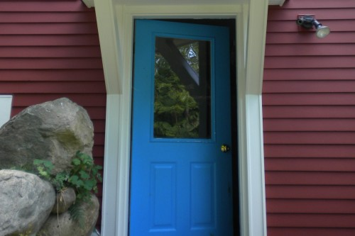 Blue door and front entrance on red house with white trim after completion of remodeling project in central vermont