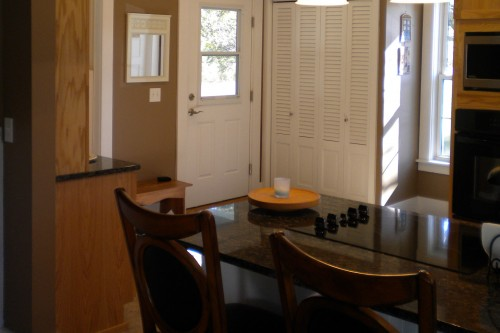 A view towards an exterior door through a furnished dining area from a completely remodeled kitchen in Barre Vermont