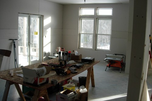 Room with tools on a work bench and installed green window during allied contractors central vermont home rebuild project