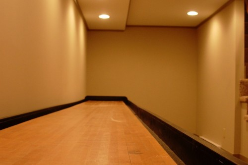 Unfurnished waitsfield basement space after remodeling project with builtin lighting and wood floors by allied builders