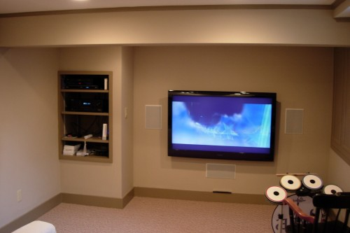 furnished waitsfield basement space after completion of remodeling project with mounted tv and shelving by allied contractors