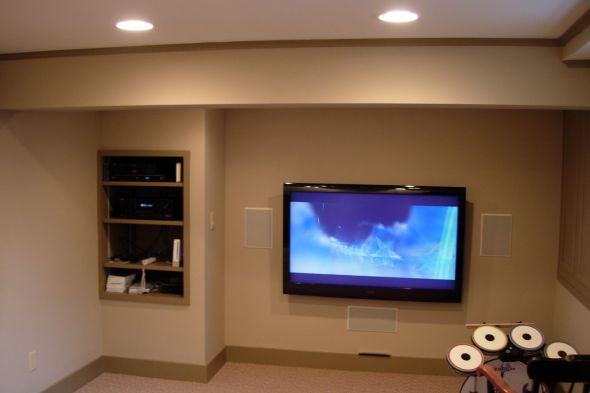 A finished basement after remodeling with built in shelving and wall mounted tv by allied contractors