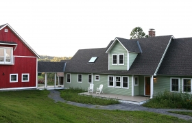 Green house and red garage in central vermont after completion of home remodeling project