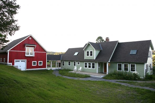 New home build with large two story green exterior and red barn in central Vermont
