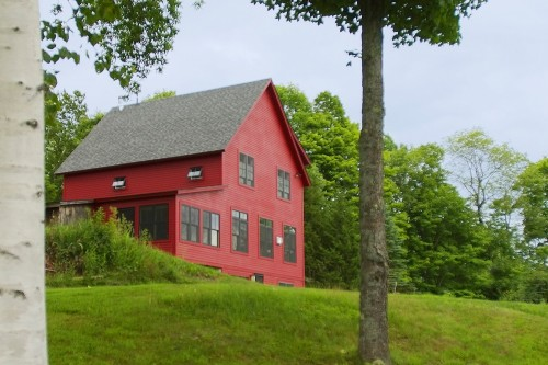 A wide shot of a fully remodeled red farm house in central vermont by allied building contractors