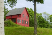 Red two story new home build perched on a hill in central Vermont
