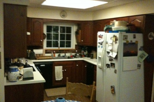 cluttered barre kitchen with white coutertops and appliances before kitchen remodeling project by allied contractors