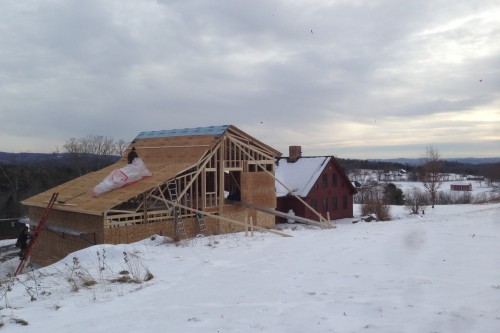 House during home remodeling project with new addition next to red additional structure in central vermont