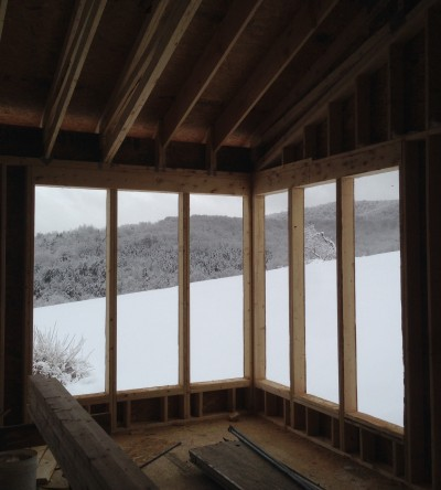 View to snowy field from gutted living area during total home renovation project in central vermont