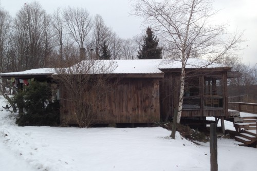 Side of a wood sided single story house in central vermont before  a full remodel by allied building contractors