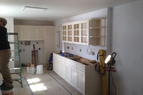 Kitchen with partially installed wood cabinets during home remodeling project