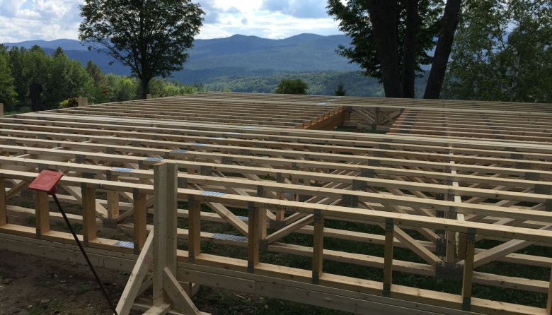 A wooden truss system laying in an outdoor yard before installation during a complete remodel of a central vermont farmhouse
