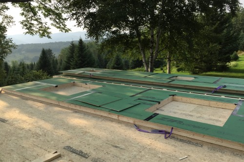 Wood walls and frames lying on the ground waiting to be installed during central vermont farmhouse remodel by allied building contractors