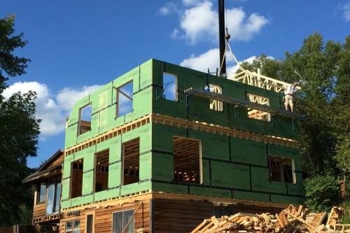 Exterior shot of central vermont farmhouse addition with green insulation during remodel process