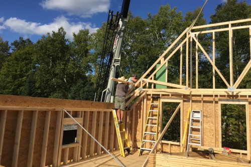 Workers installing a wooden frame for a new addition on a central vermont farmhouse during a full remodel