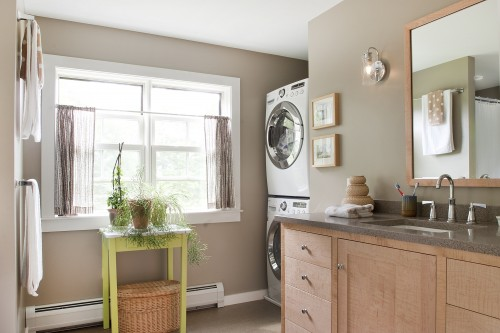 A bright fully remodeled laundry room with large windows washer and drier combo and wood cabinets