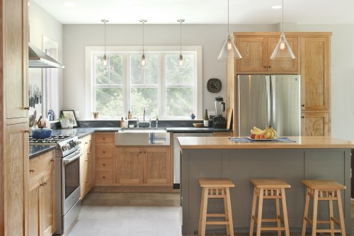 A completely remodeled bright and modern kitchen with an island and modern appliances in a central vermont farmhouse