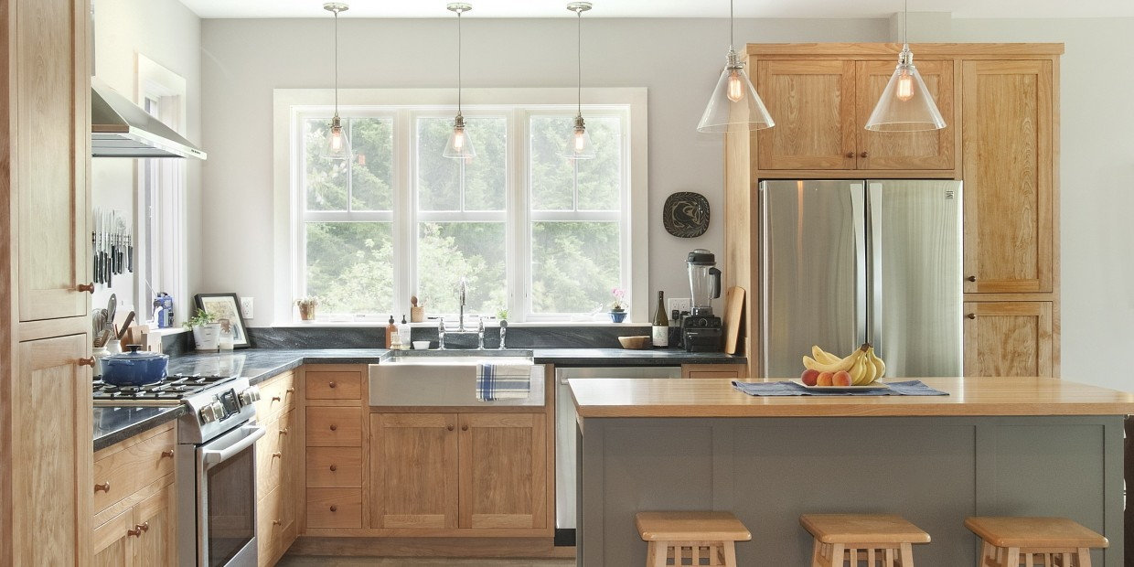 A fully remodeled kitchen with bright windows and modern appliances in renovated central vermont farmhouse