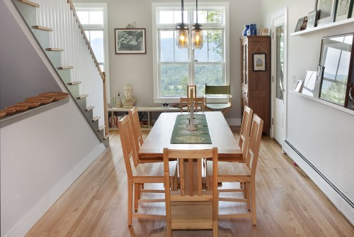 A furnished fully remodeled dining room with long table looking out on large windows in central vermont farmhouse