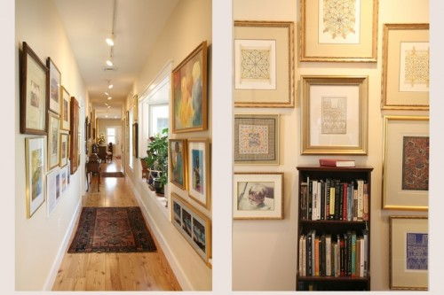 view down long hallway lined with framed pictures in completed home build project in central vermont