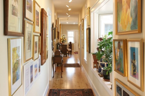 New home build hallway with framed photos and area rugs in central vermont project by allied builders