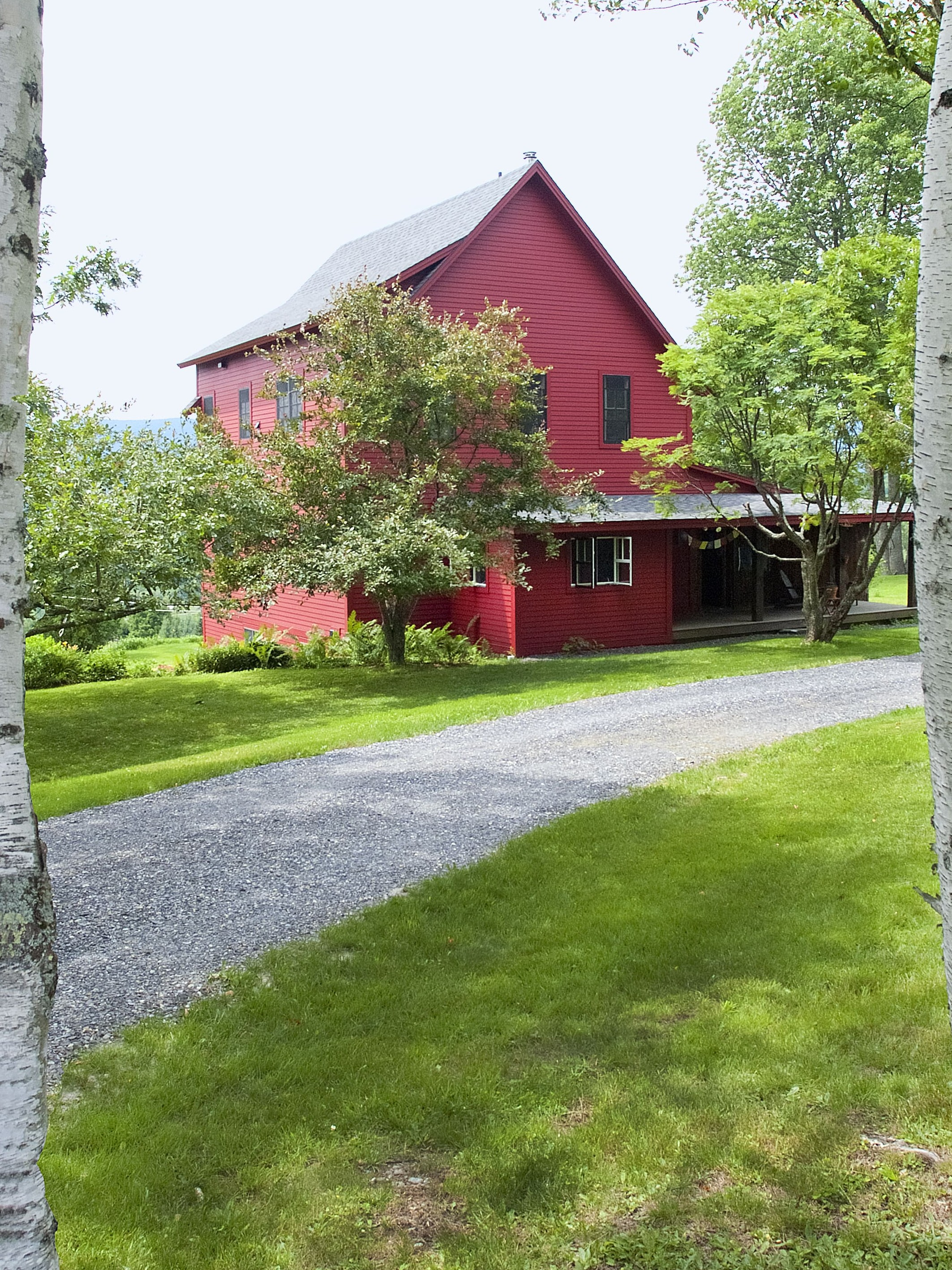 A wide shot of a fully remodeled two story red central vermont farmouse