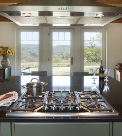 View of remodeled kitchen in central vermont house after complete remodel with view over stove towards large windows looking into green hills