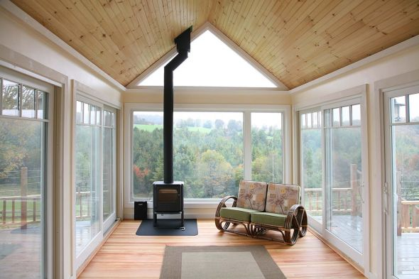 A large living space with a wood stove, couch and green energy efficient windows on all sides looking over hills in Central Vermont