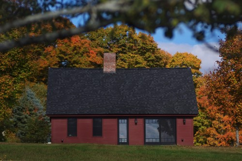exterior view of red house in front of fall trees after completion of remodeling project in central vermont