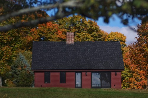 Wide view of red house in front of autumn trees in central vermont after complete remodeling project