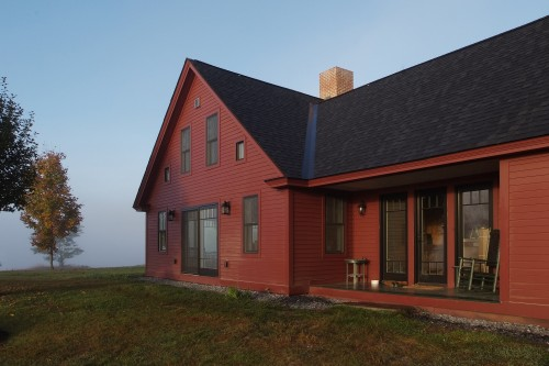 Exterior of red house with new windows after home remodeling project in central vermont